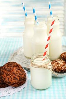 Milch in flaschen mit papierstrohhalmen auf dem tisch