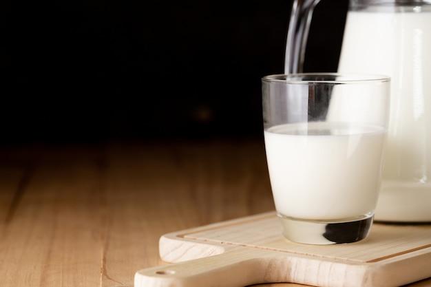 Milch in glas und krug auf holztisch
