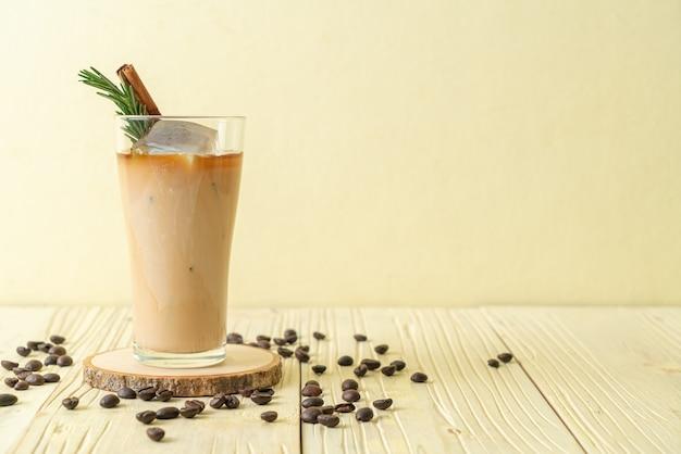 Milch in schwarzes kaffeeglas mit eiswürfel, zimt und rosmarin auf holztisch gießen
