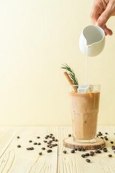 Milch in schwarzes kaffeeglas mit eiswürfel, zimt und rosmarin gießen