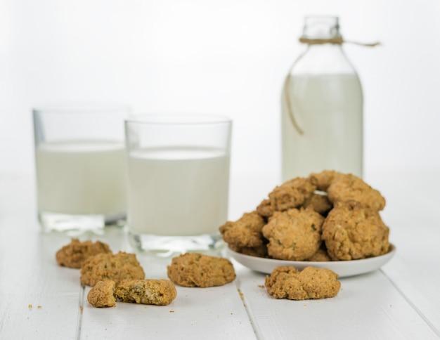Milch in zwei gläsern und schüssel mit hausgemachten keksen.