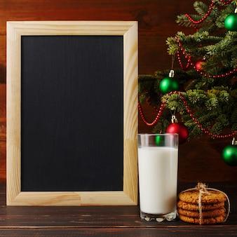 Milch, kekse und eine wunschliste unter dem weihnachtsbaum. die ankunft des weihnachtsmannes.