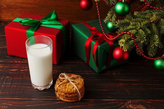 Milch, kekse und geschenke unter dem weihnachtsbaum. die ankunft des weihnachtsmannes.