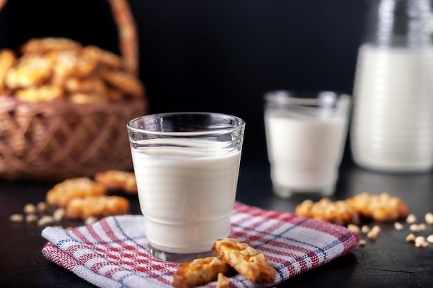 Milch mit frisch gebackenen hausgemachten erdnusskeksen auf dunkler oberfläche