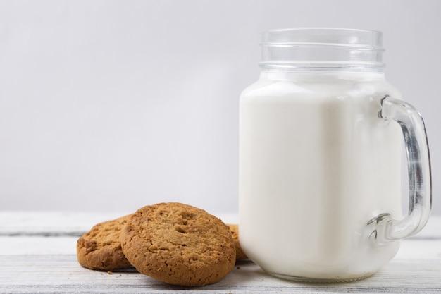 Milch mit plätzchen auf hölzernem weißem hintergrund
