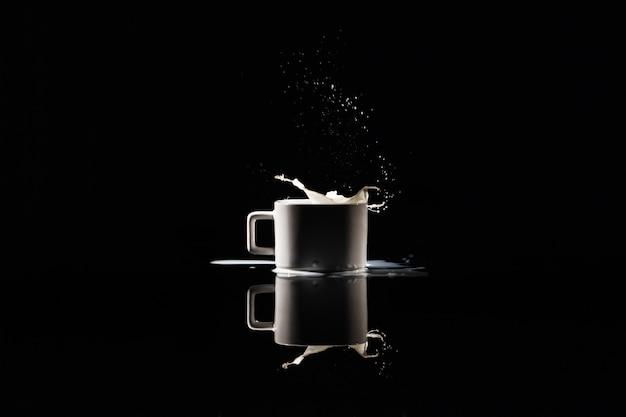 Milch spritzt in der weißen schale auf schwarzem hintergrund