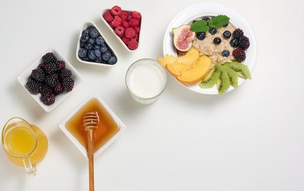 Milch, teller mit haferbrei und obst, frisch gepresster saft in einem transparenten glasdekanter, honig in einer schüssel auf einem weißen tisch. gesundes frühstück