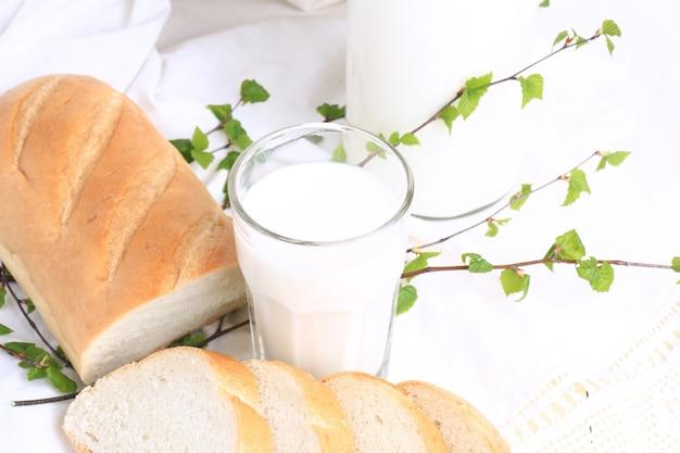 Milch und brot auf einem weißen spitzenhintergrund bio-bio-produkt frisches gebäck gesunder lebensstil