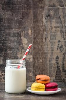Milch und farbige makronen auf rustikalem hölzernem hintergrund