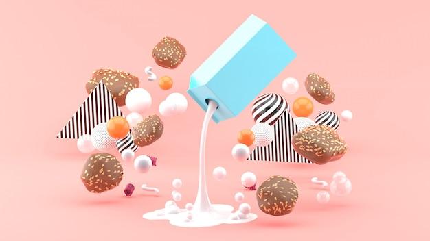 Milch und kekse zwischen den bunten kugeln auf dem rosa raum