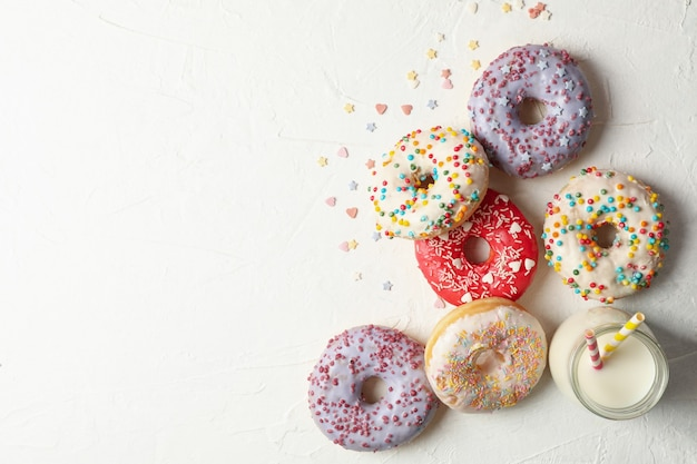 Milch und leckere donuts auf weißer draufsicht