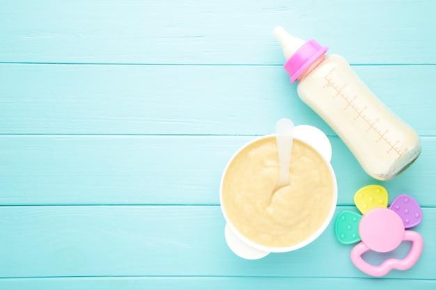 Milch und schüssel mit brei für baby auf blau