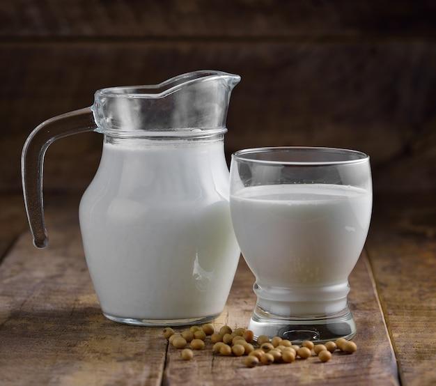 Milch und soja in einem glas auf holztisch