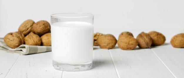 Milch von walnüssen und nüssen auf einem weißen hölzernen hintergrund. produkte, die pflanzliches protein, vitamine und nützliche aminosäuren enthalten. speicherplatz kopieren.
