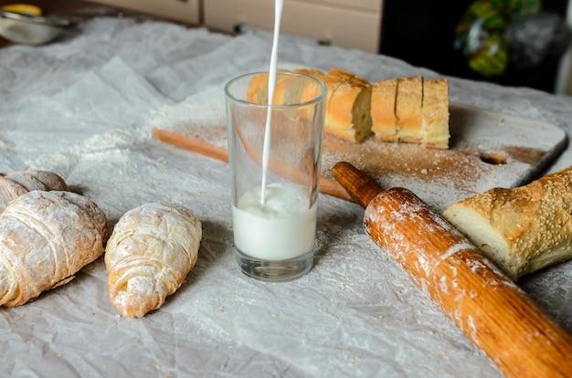 Milch wird in ein glas, brot, croissants gegossen