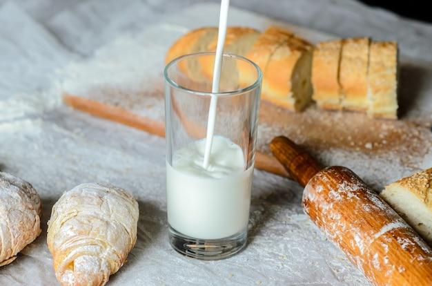 Milch wird in ein glas gegossen, brot, croissants