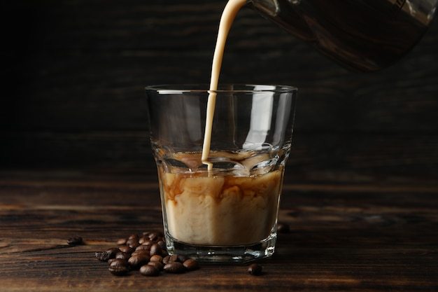 Milch wird in ein glas kaffee gegossen. zusammensetzung mit eiskaffee