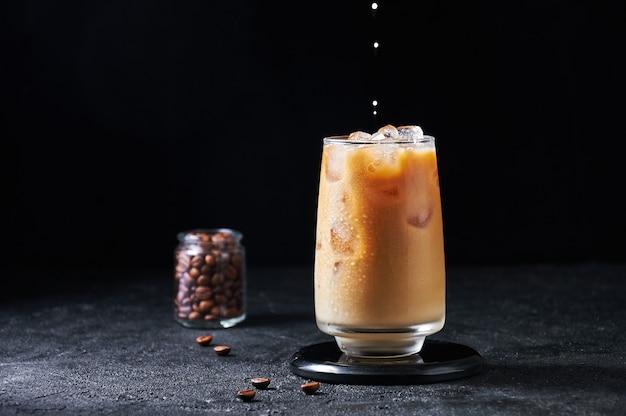 Milch wird in eiskaffee im hohen glas auf dunklem hintergrund gegossen. konzept erfrischendes sommergetränk.