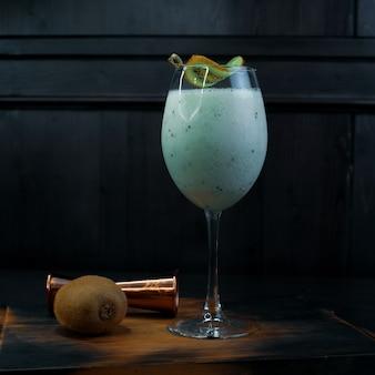 Milchalkoholischer cocktail mit pinot-colada und kokosnusssirup, dekoriert mit einer scheibe kiwi, steht in einem eleganten glas auf einem hölzernen vintage-tisch neben einem metallglas und kiwi. leckeres süßes getränk.