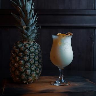 Milchalkoholischer cocktail mit saft mit eiswürfeln mit obstscheiben und tonic mit wodka und sahne steht in einem eleganten glas auf einem vintage-tisch in der nähe einer frischen ananas in der bar. exotische getränke.