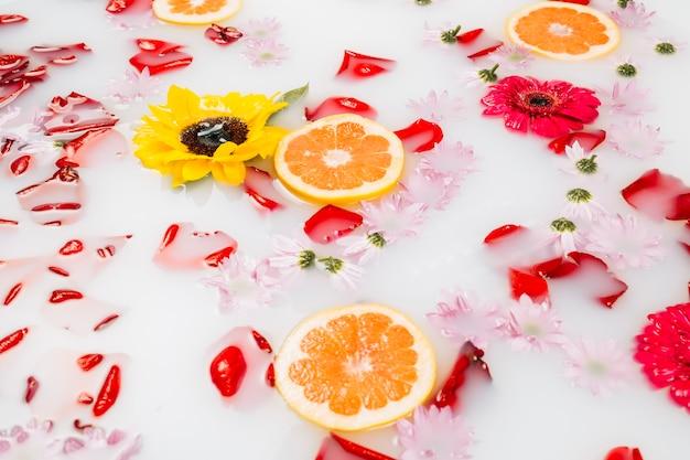 Milchbad mit verschiedenen blumen, blütenblättern und grapefruitscheiben