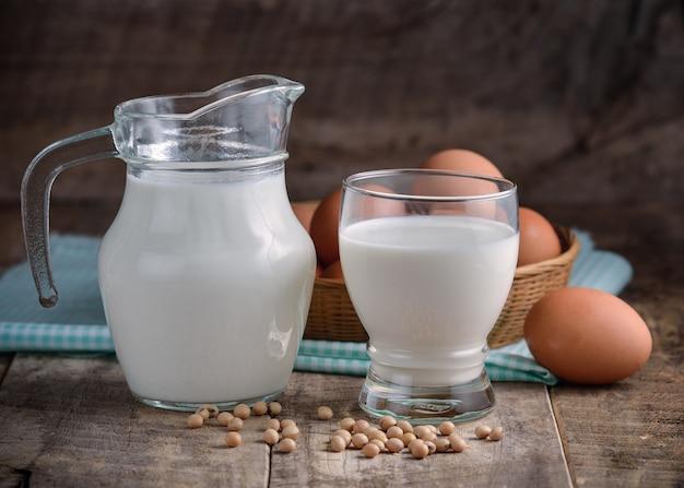 Milchei und soja in einem glas auf holz