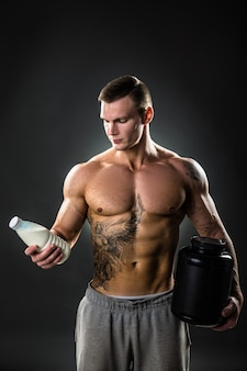 Milchflasche in den händen eines sportlers, gesunder mann mit der richtigen lebensweise. tätowieren