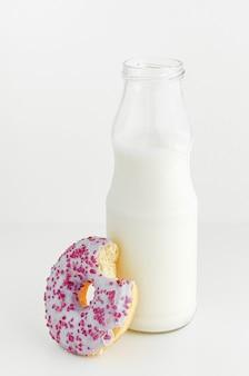 Milchflasche- und fruchtaromadonut mit biss auf weißem hintergrund