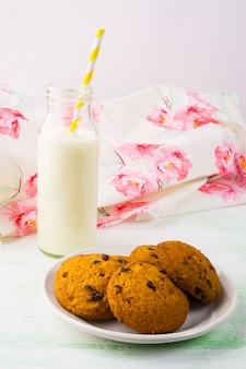 Milchflasche und plätzchen auf der weißen platte, vertikal