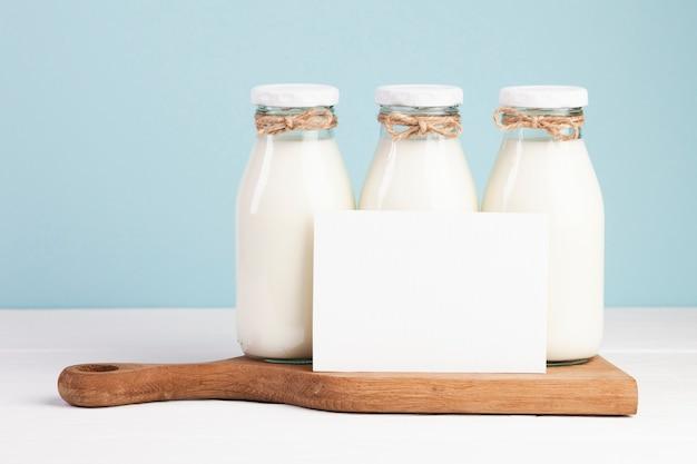 Milchflaschen und karte auf schneidebrett