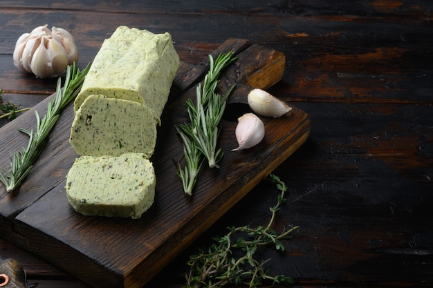 Milchgrüne butter mit kräutern auf altem dunklem holztisch