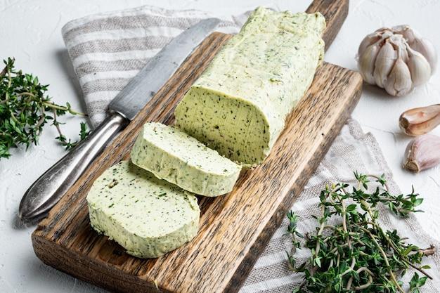 Milchgrüne butter mit kräutern auf weißem stein