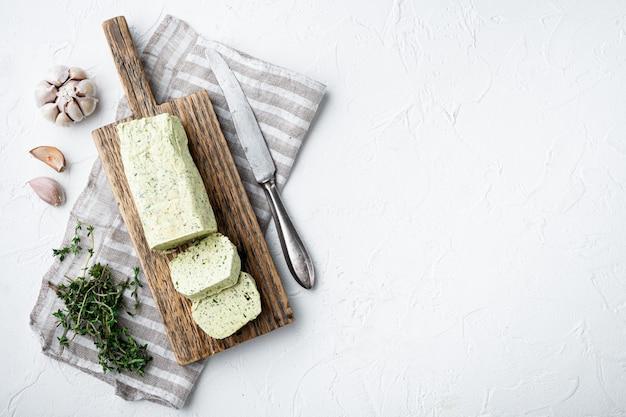 Milchgrüne butter mit kräutern auf weißem steintisch