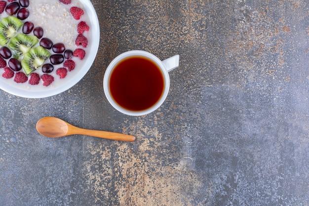 Milchiger porridge mit beeren und einer tasse tee