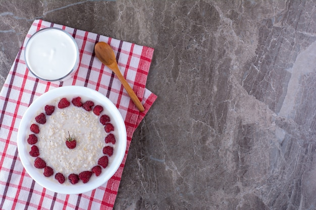 Milchiger porridge mit himbeeren und einer tasse sahne