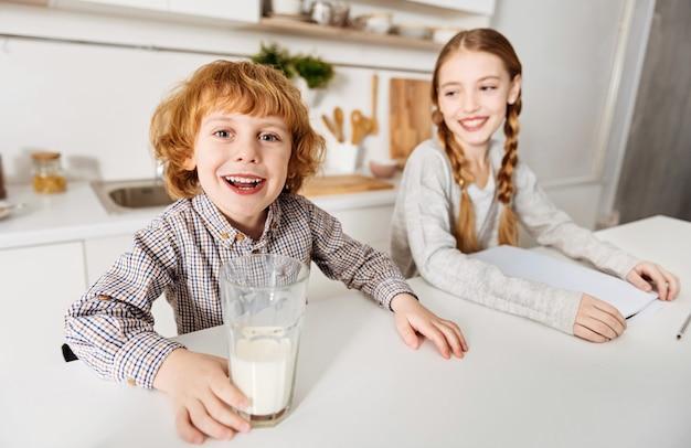 Milchiger schnurrbart. fröhliche, charmante, entzückende geschwister, die ihren gemeinsamen tag beginnen, während der junge, der milch trinkt, und seine schwester ihre hausaufgabe erledigen