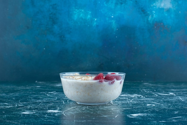 Milchiger smoothie mit früchten und beeren in einer glasschale.