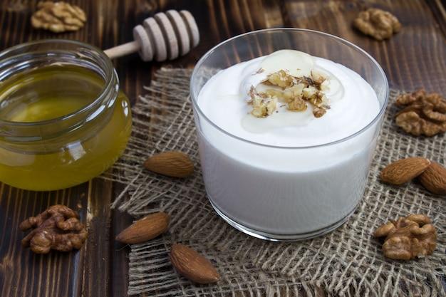 Milchjoghurt mit honig und nüssen auf dem rustikalen hölzernen hintergrund