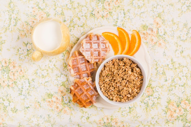 Milchkännchen und teller mit gesunder müslischüssel mit waffeln und orangenscheibe