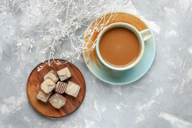Milchkaffee der draufsicht mit schokoladenwaffeln auf dem süßen zuckerkuchen-keks des grauen schreibtisches