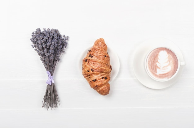 Milchkaffee mit croissant auf weißem holztisch und getrockneter violetter lavendelblüte. draufsicht