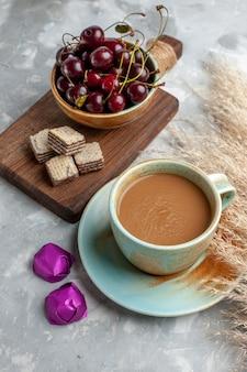 Milchkaffee mit waffeln und frischen sauerkirschen auf leichtem schreibtisch