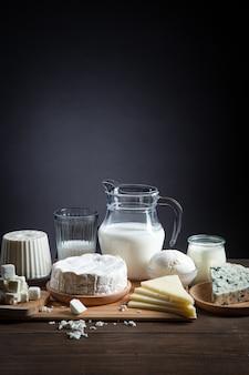 Milchprodukte auf holzsockel und dunklem hintergrund mit kopierraum, vertikales format.
