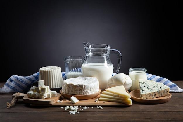 Milchprodukte auf holzsockel und dunklem hintergrund mit kopierraum.