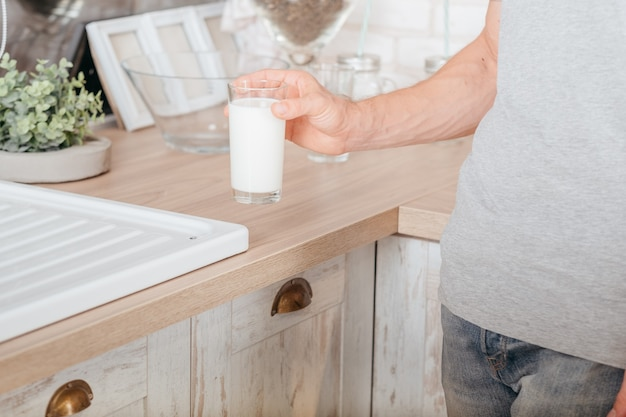 Milchprodukte. gesunder lebensstil. kurzer schuss des mannes, der glas sojamilch nimmt. küchenwand.