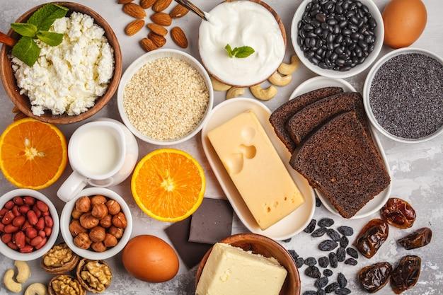 Milchprodukte, hülsenfrüchte, eier, nüsse, schokolade, mohn, sesam, schokolade. weißer hintergrund, ansicht von oben