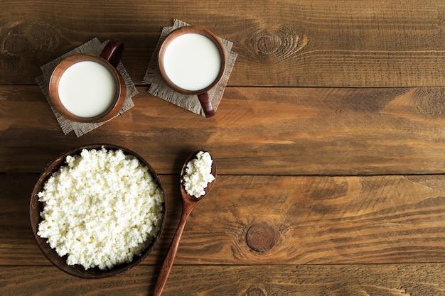 Milchprodukte hüttenkäse und milch in holzschalen draufsicht auf holz