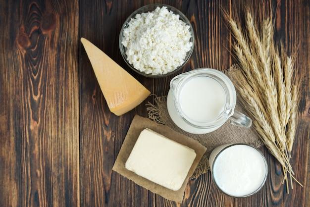 Milchprodukte. milch, kefir, butter, hüttenkäse, eier und käse mit ähren auf dunklem holzhintergrund.