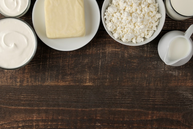 Milchprodukte. milch, sauerrahm, käse, butter und hüttenkäse auf einem braunen holztisch. ansicht von oben. rahmen. platz für text
