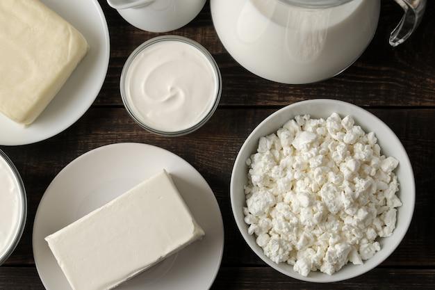 Milchprodukte. milch, sauerrahm, käse, butter und hüttenkäse auf einem braunen holztisch. ansicht von oben